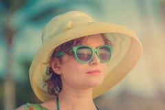 Junges Mädchen auf dem Strand in den grünen Gläsern während des Sonnenuntergangs lizenzfreie stockfotografie