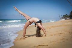 Junges Mädchen auf dem Strand, der Morgen excercises tut Stockfoto