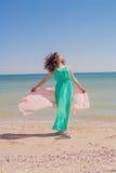 Junges Mädchen auf dem Strand im Sommer mit einem Fliegenschal Stockfotografie