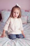 Junges Mädchen auf einem Bett Stockfotos