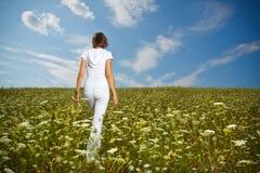 Junges Mädchen auf einem Blumengebiet Lizenzfreie Stockfotos