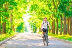 Junges Mädchen auf einem Fahrrad in einem Park Lizenzfreie Stockfotos