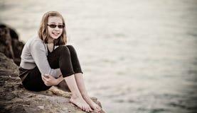 Junges Mädchen auf einem Felsen Stockbilder
