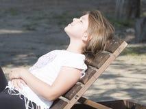 Junges Mädchen auf einem Klappstuhl Lizenzfreie Stockbilder