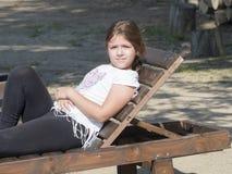 Junges Mädchen auf einem Klappstuhl Lizenzfreies Stockfoto