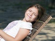 Junges Mädchen auf einem Klappstuhl Stockfotografie