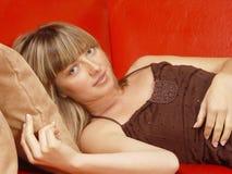 Junges Mädchen auf einem roten Sofa Stockfotografie