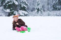 Junges Mädchen auf einem Schneeschlitten Lizenzfreies Stockbild