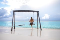 Junges Mädchen auf einem Schwingen über Wasser stockfotografie