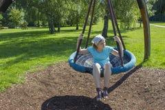 Junges Mädchen auf Schwingen im Park Stockfoto