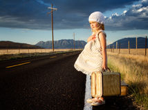 Junges Mädchen auf Seite der Straße mit Koffern Lizenzfreie Stockfotos