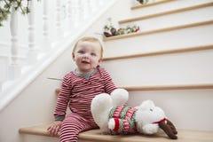Junges Mädchen auf Treppe in den Pyjamas am Weihnachten Stockbild