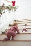 Junges Mädchen auf Treppe in den Pyjamas am Weihnachten Lizenzfreies Stockbild