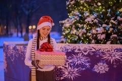 Junges Mädchen auf Weihnachtsabend unter dem Weihnachtsbaum Stockfoto