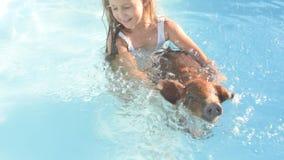 Junges Mädchen in Badeanzug schwimmt im klaren, blauen Wasser des Pools mit rotem Schwein von Duroczucht 2019-jährig vom gelben S stock video