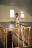 Junges Mädchen basiert auf geschnitztem hölzernem Geländer Stockbild