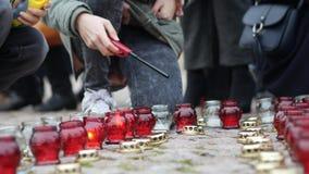 Junges Mädchen beleuchtet eine votive Kerze stock footage