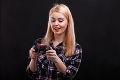 Junges Mädchen betrachtet faszinierend die Platte des Spielsteuerknüppels Auf einem schwarzen Hintergrund stockfoto