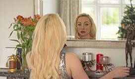 Junges Mädchen bewundert sich im Spiegel über einem Kamin Lizenzfreies Stockfoto