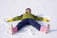 Junges Mädchen bildet einen Schnee-Engel Lizenzfreies Stockbild