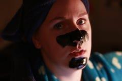 Junges Mädchen 20 bis 25 mit einer Holzkohlenmaske auf Gesicht als Teil des Schönheitsregimes nachdem dem Duschen Stockbild