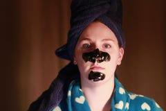 Junges Mädchen 20 bis 25 mit einer Holzkohlenmaske auf Gesicht als Teil des Schönheitsregimes nachdem dem Duschen Lizenzfreie Stockfotos