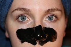 Junges Mädchen 20 bis 25 mit einer Holzkohlenmaske auf Gesicht als Teil des Schönheitsregimes nachdem dem Duschen Stockbilder