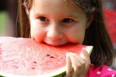 Junges Mädchen Brunette isst eine enorme Scheibe der roten Wassermelone Stockfotos