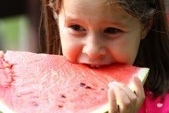 Junges Mädchen Brunette isst eine enorme Scheibe der Wassermelone Lizenzfreie Stockbilder