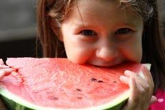 Junges Mädchen Brunette isst eine große Scheibe der roten Wassermelone Stockfotos