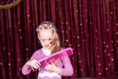 Junges Mädchen-Clown Brushing Hair mit großem Kamm Stockbilder