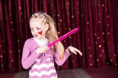 Junges Mädchen-Clown Brushing Hair mit großem Kamm Stockfoto
