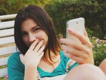 Junges Mädchen, das über ihr intelligentes Telefon lacht Stockfotos