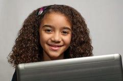 Junges Mädchen, das über Laptop schaut Stockbilder