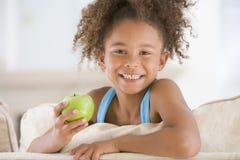 Junges Mädchen, das Apfel beim Wohnzimmerlächeln isst Stockfoto