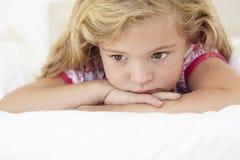 Junges Mädchen, das auf Bett im Schlafzimmer traurig schaut Stockfotografie
