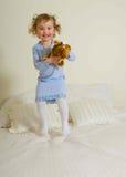 Junges Mädchen, das auf Bett springt Lizenzfreie Stockfotografie