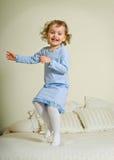 Junges Mädchen, das auf Bett springt Lizenzfreie Stockbilder