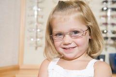 Junges Mädchen, das auf Brillen an den Optometrikern versucht Stockbild