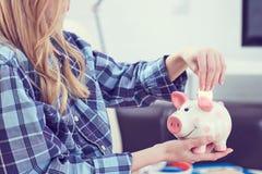 Junges Mädchen, das auf Couch sitzt und litecoin in piggybank einsetzt stockbild