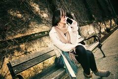 Junges Mädchen, das auf dem Bankdenken sitzt Stockfotografie