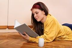 Junges Mädchen, das auf dem Boden liest ein Buch liegt Stockbilder