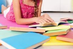 Junges Mädchen, das auf dem Boden mit vielen Büchern liegt Lizenzfreies Stockfoto