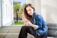 Junges Mädchen, das auf dem Collegecampusyard sitzt Stockfoto