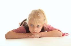 Junges Mädchen, das auf dem Fußboden liegt Stockfotografie