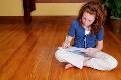 Junges Mädchen, das auf dem Fußbodenschreiben sitzt Stockfotografie
