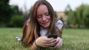 Junges Mädchen, das auf dem grünen Gras und dem Gebrauch Smartphone, sms, simsend liegt stock video