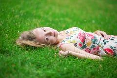 Junges Mädchen, das auf dem Gras an einem Sommertag liegt Lizenzfreie Stockfotografie