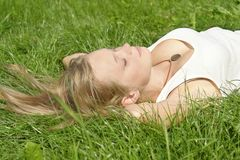 Junges Mädchen, das auf dem Gras liegt Stockfotografie