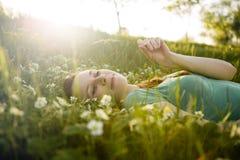 Junges Mädchen, das auf dem Gras liegt Lizenzfreie Stockfotos